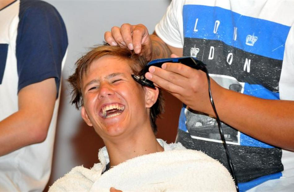 Otago Boys' High School pupil Ted Brown (17) laughs as his head is shaved. Photo by Gregor...