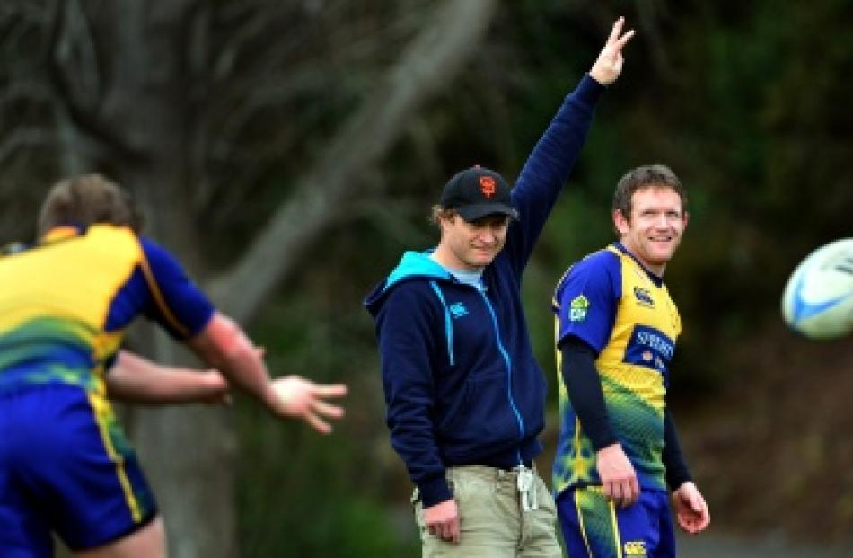 Otago coach Tony Brown makes a signal with first five-eighth Peter Breen beside him at training...