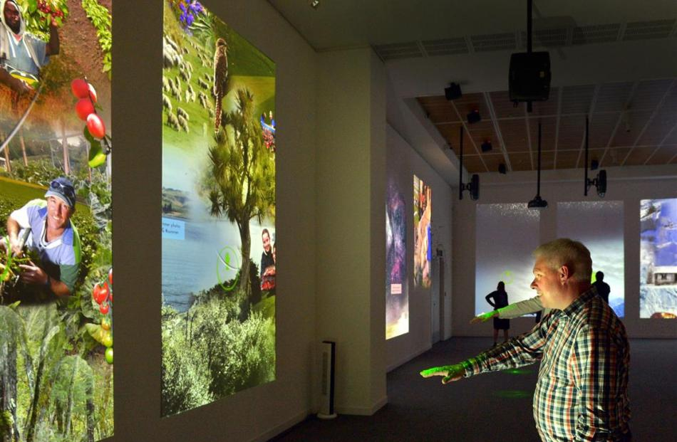 Otago Museum director Dr Ian Griffin uses the ''laser gesture control system'' in the museum's...