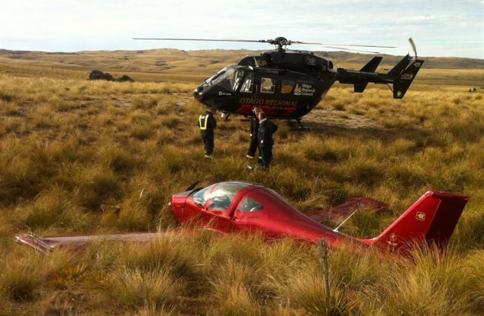 Otago Regional Rescue Helicopter crew check  the pilot of the microlight that crash-landed near...