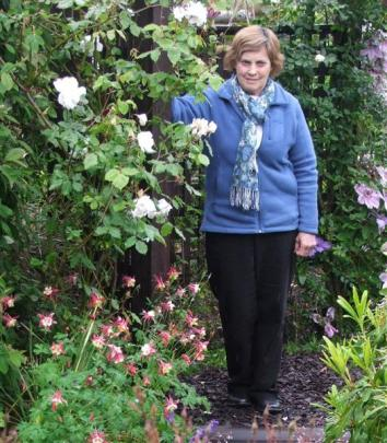 Otago Rose Society secretary Marilyn Langford in her Dunedin garden. She is standing by a...