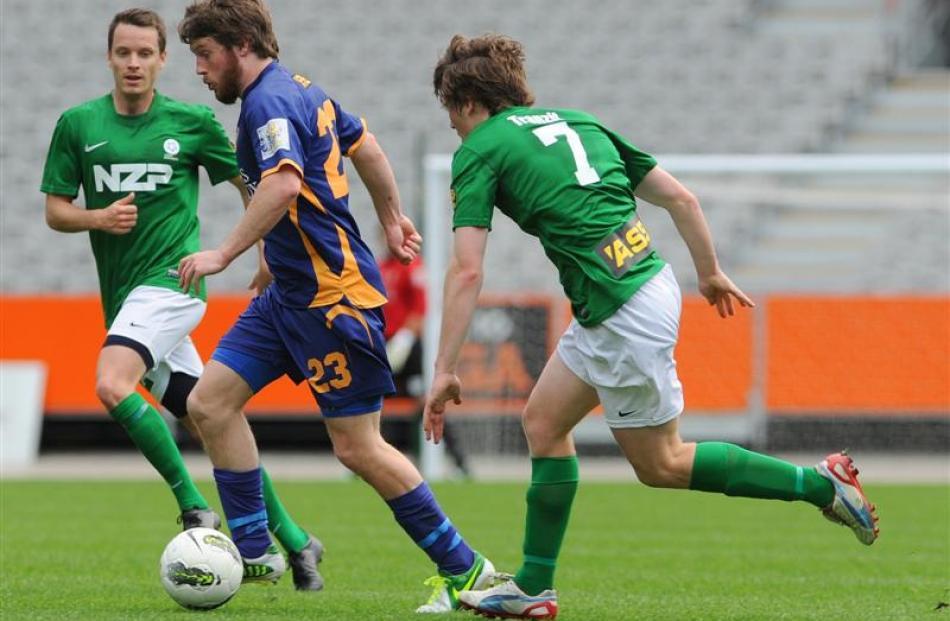 Otago United midfielder Regan Coldicott streaks past Manawatu defenders Grant Robson (left) and...