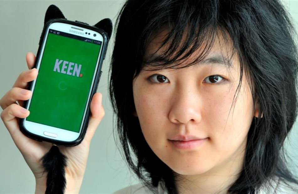 Otago University student Scout Lin (23) holds  a smartphone running a social networking...