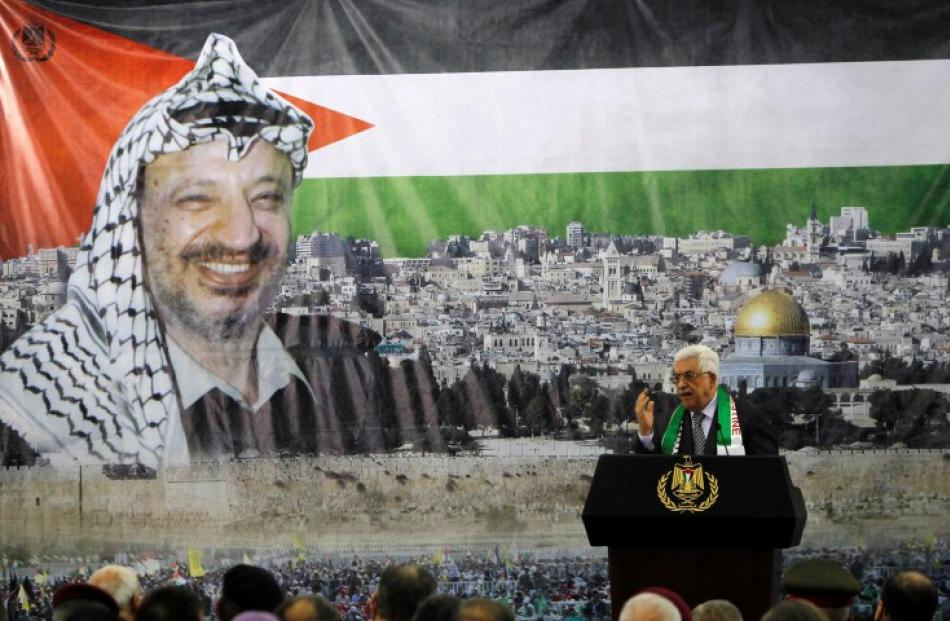 Palestinian President Mahmoud Abbas stands in front of a banner with a picture of late...