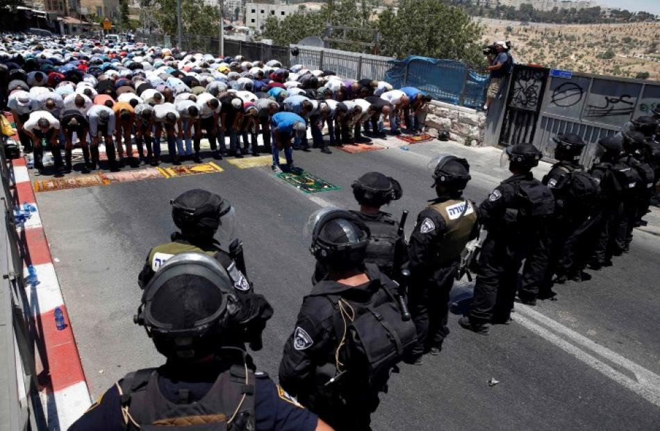 Palestinians pray on the first Friday of the holy month of Ramadan as Israeli policemen stand...