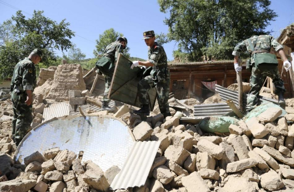 Paramilitary policemen search for victims amongst collapsed houses after a 6.6 magnitude...