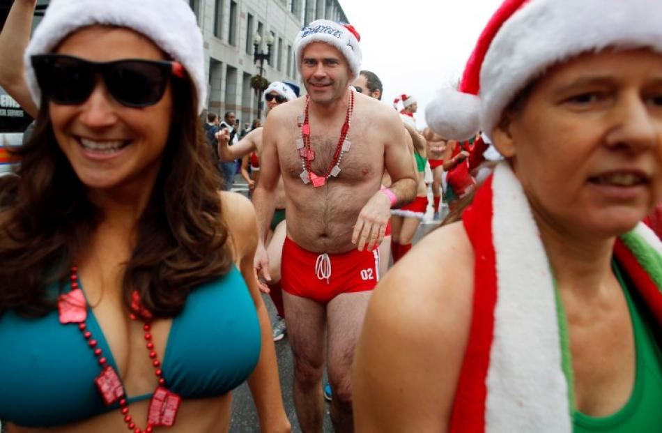 Participants leave the starting line in the annual 'Santa Speedo Run', a charity race through the...