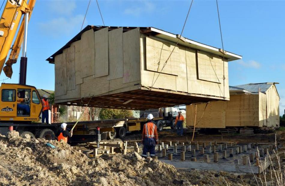 Patterson Contracting workers lower a house relocated from Christchurch's red zone on to its...