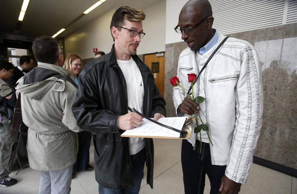 Paul Mattson and Roland Smith fill out paperwork as they stand in line for a marriage license at...