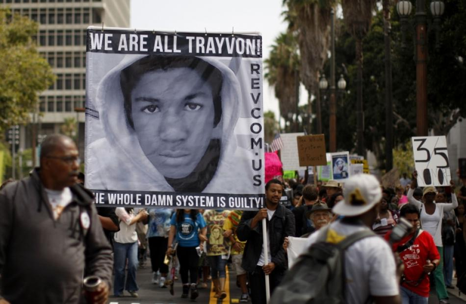 People carry a photo of Trayvon Martin during a march to protest the verdict in the George...