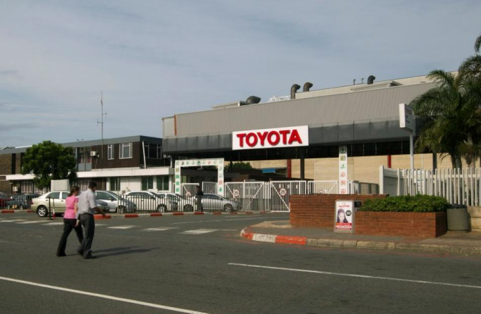 People walk near Toyota's Durban factory, which has been forced to shut down for four days due to...
