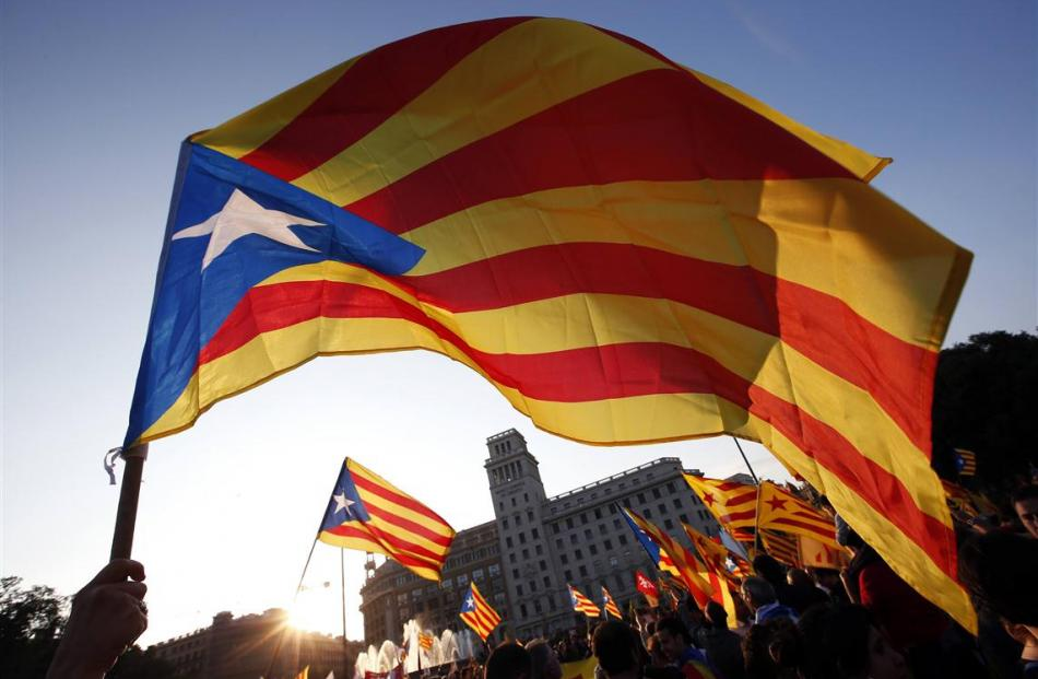 People wave Catalan separatist flags during an anti-royalist demonstration at Catalunya square in...