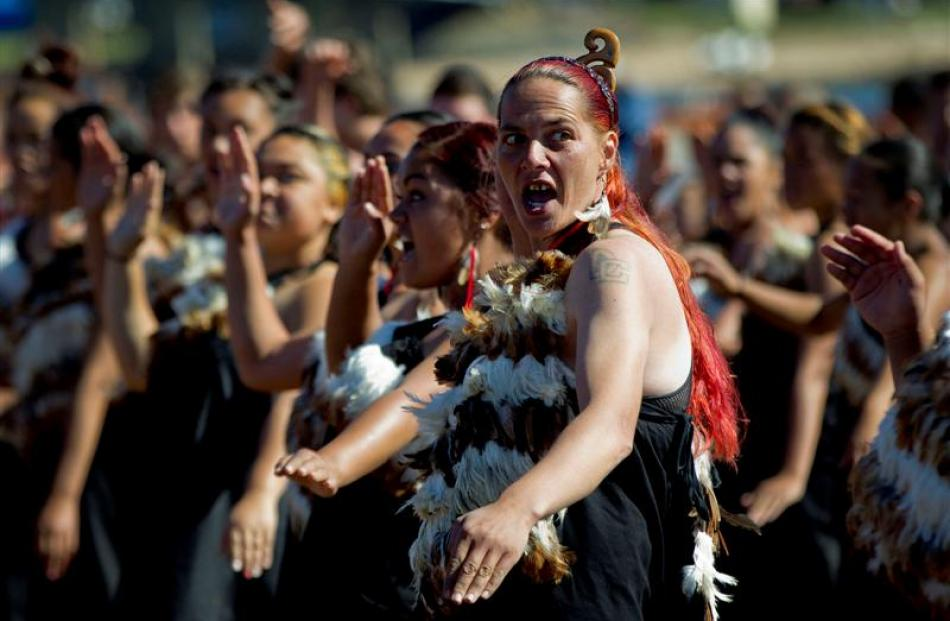 Women and men perform a haka on the beach.