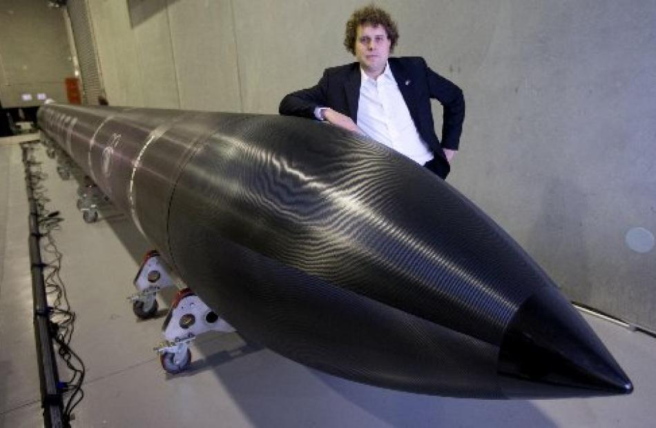 Peter Beck with his Electron rocket in Auckland yesterday. Photo NZ Herald