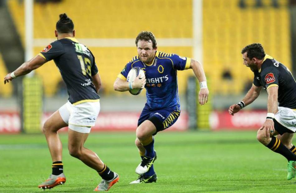 Peter Breen of Otago runs at Matt Proctor (left) and Jonny Bentley of Wellington during the ITM...