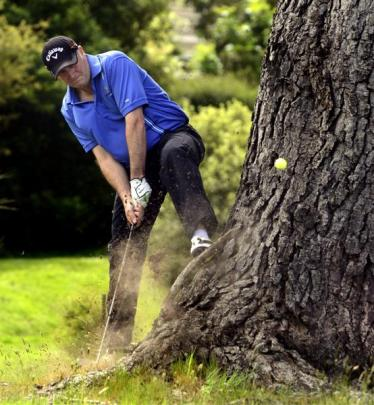 Playing from the rough, Prime Minister John Key tackles a tricky shot on the third hole during a...