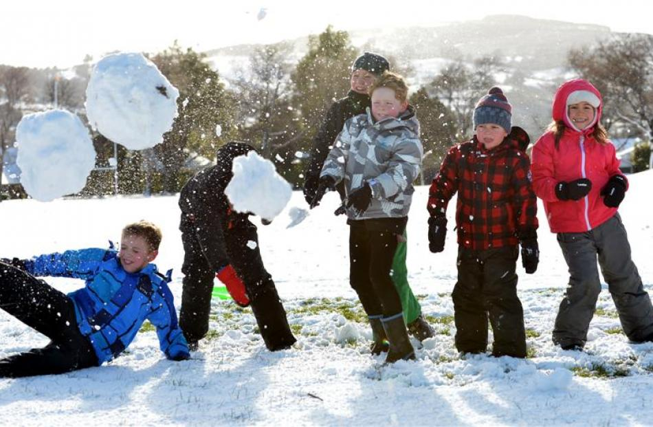 Playing in the snow at John McGlashan College yesterday are (from left) Peter MacNab (9), Ollie...