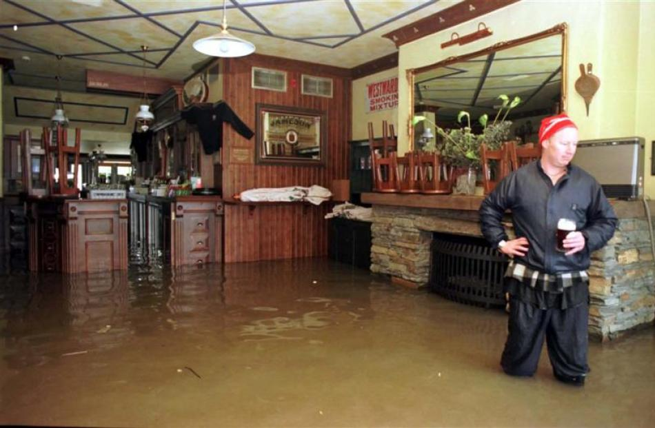 Pog Mahones bar worker Paul Murphy surveys flood damage in the Rees St bar during the 1999...