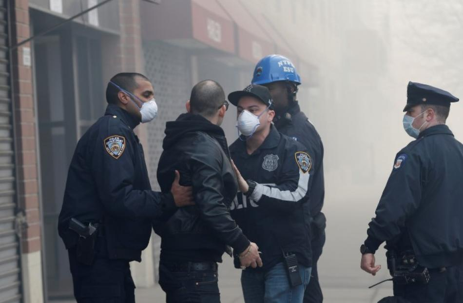 Police and emergency personnel attend to a man on East 116th street near the site of the...
