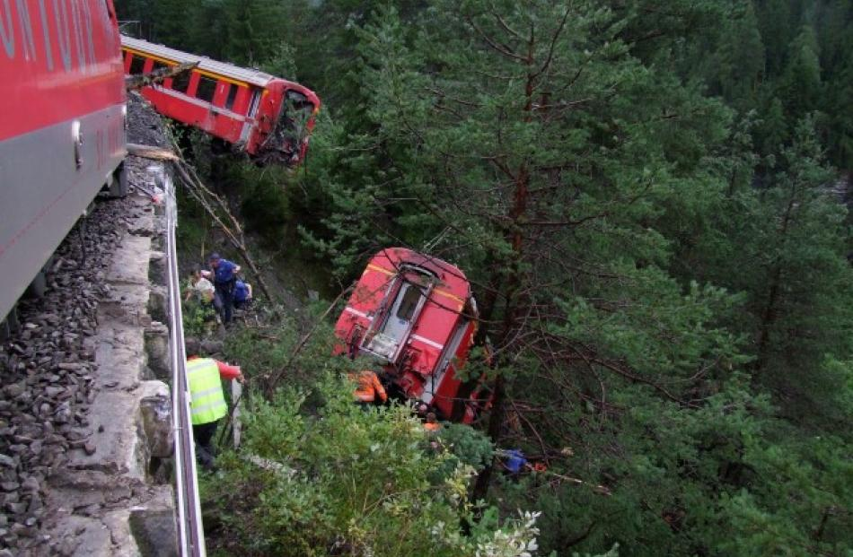 Police and rescue workers help after the train derailed into a ravine near Tiefencastel in a...