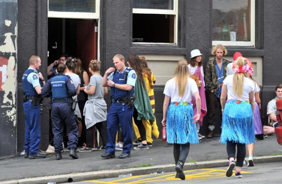 Police enter a flat party in Stafford St yesterday following reports of disorder. Photo by Linda...
