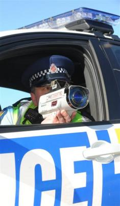 Police officers check on traffic and motorists' behaviour yesterday on the Southern Motorway....