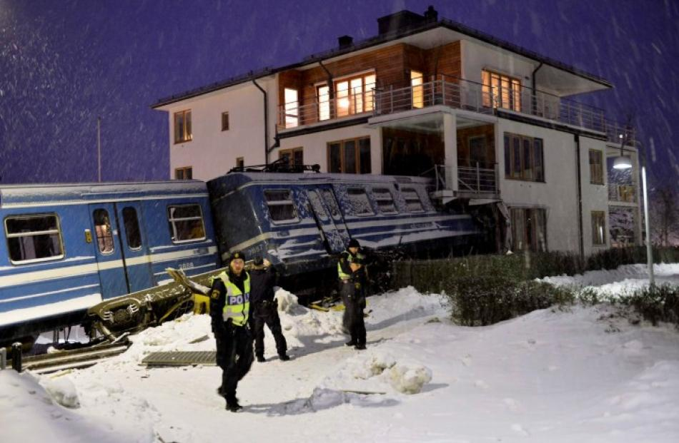 Police officers stand around a stolen train that derailed and crashed into a residential building...