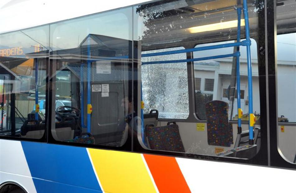 Police talk to the driver of a passenger bus that was allegedly shot at yesterday morning.  Photo...