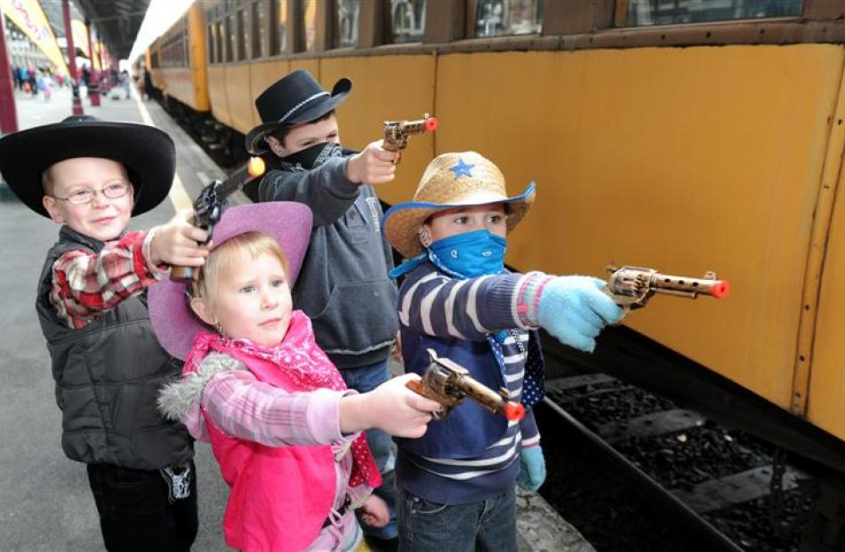 Practising their bandit apprehension skills before boarding the Taieri Gorge train yesterday are ...