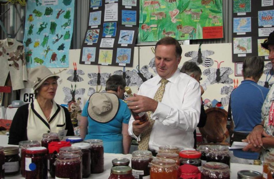 Prime Minister John Key admires a bottle of wine with Wanaka's Jan Allen (left) at the  home...