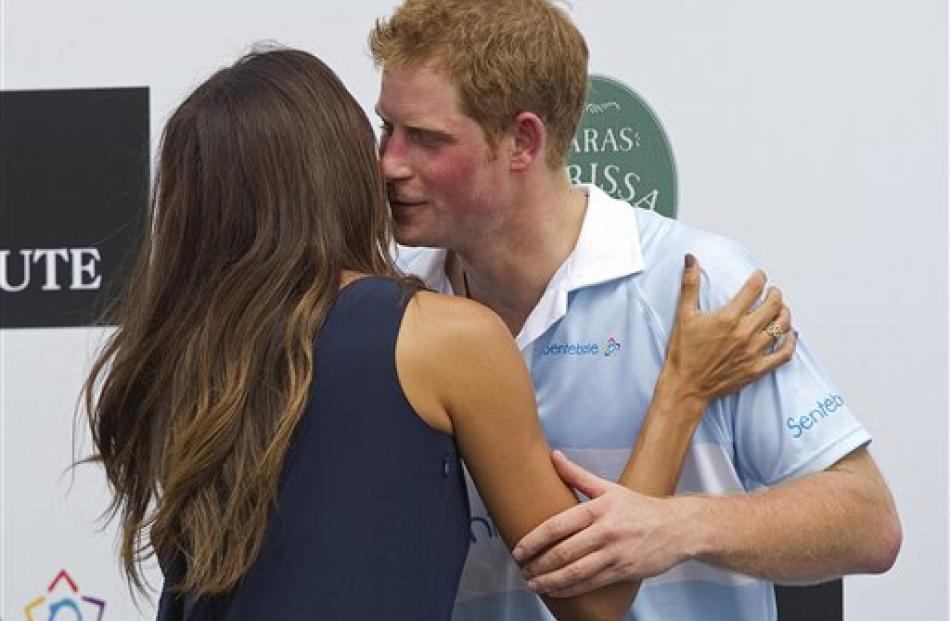 Prince Harry greets Brazilian model Fernanda Motta after a charity polo match in Campinas as part...