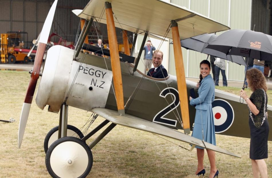 Prince William, Duke of Cambridge climbs in to the cockpit of a WWI bi-plane as Catherine,...
