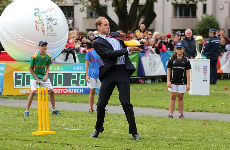 Prince William, Duke of Cambridge plays a game of cricket during a visit to Latimer Square in...