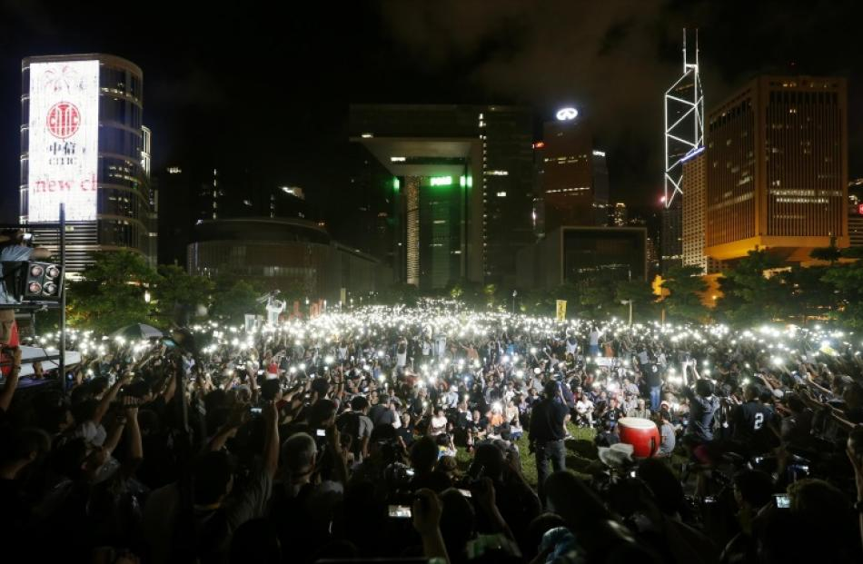 Pro-democracy protesters switch on their mobile phones during a campaign to kick off the Occupy...