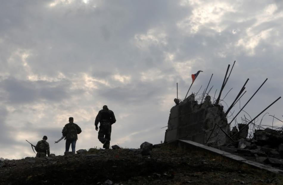 Pro-Russian separatists walk at a destroyed war memorial on Savur-Mohyla, a hill east of the city...