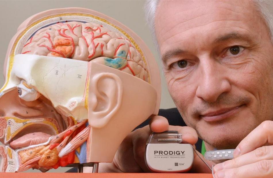 Prof Dirk De Ridder with a  brain  implant and an external activation device. Photo: Gerard O'Brien