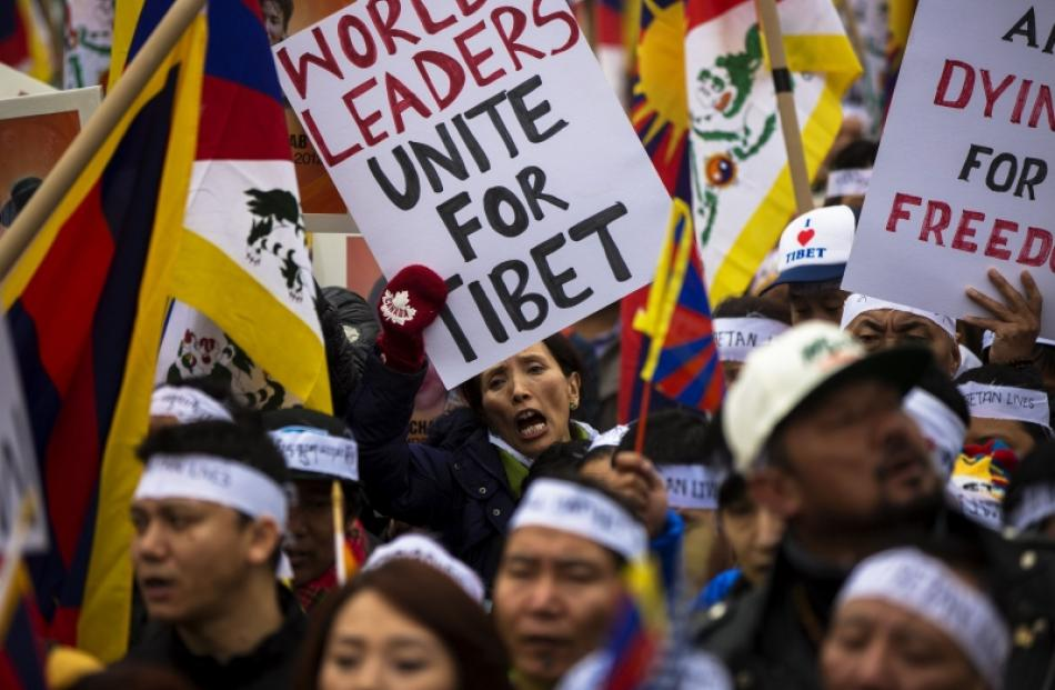 Protesters chant and hold placards as they take part in a solidarity march in support of Tibet...