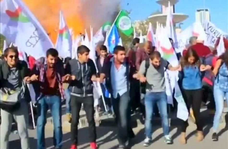 Protesters dance during a peace rally as a blast goes off in Ankara, Turkey at the weekend in...