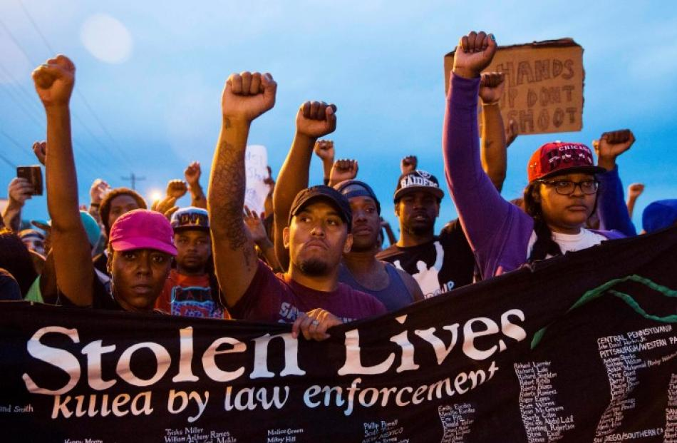 Protesters march during ongoing demonstrations in reaction to the shooting of Michael Brown in...
