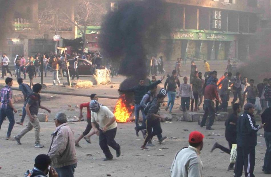 Protesters run during clashes with police in Ain Shams area east of Cairo. REUTERS/Al Youm Al...