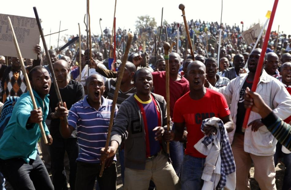 Protesters sing as they hold weapons outside a South African mine in Rustenburg, 100km northwest...