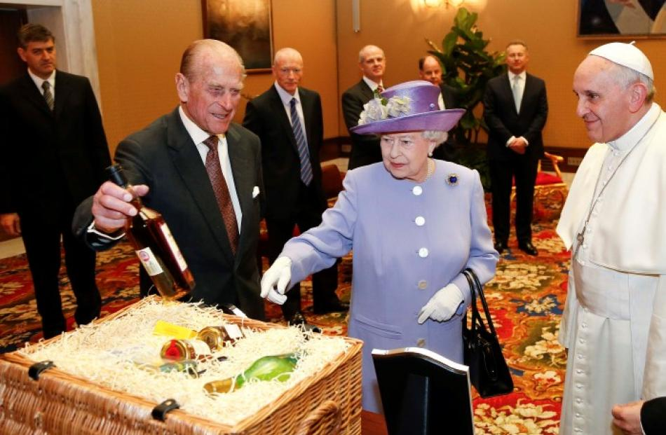Queen Elizabeth (C) and Prince Philip (L) present gifts to Pope Francis during their meeting at...