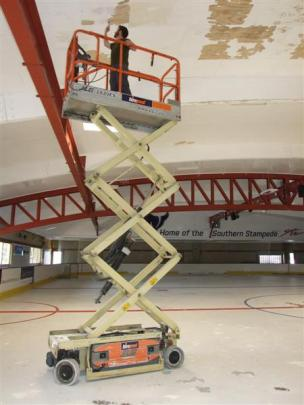 Queenstown Ice Arena co-owner Ted Graham paints the  rink's ceiling where condensation has...