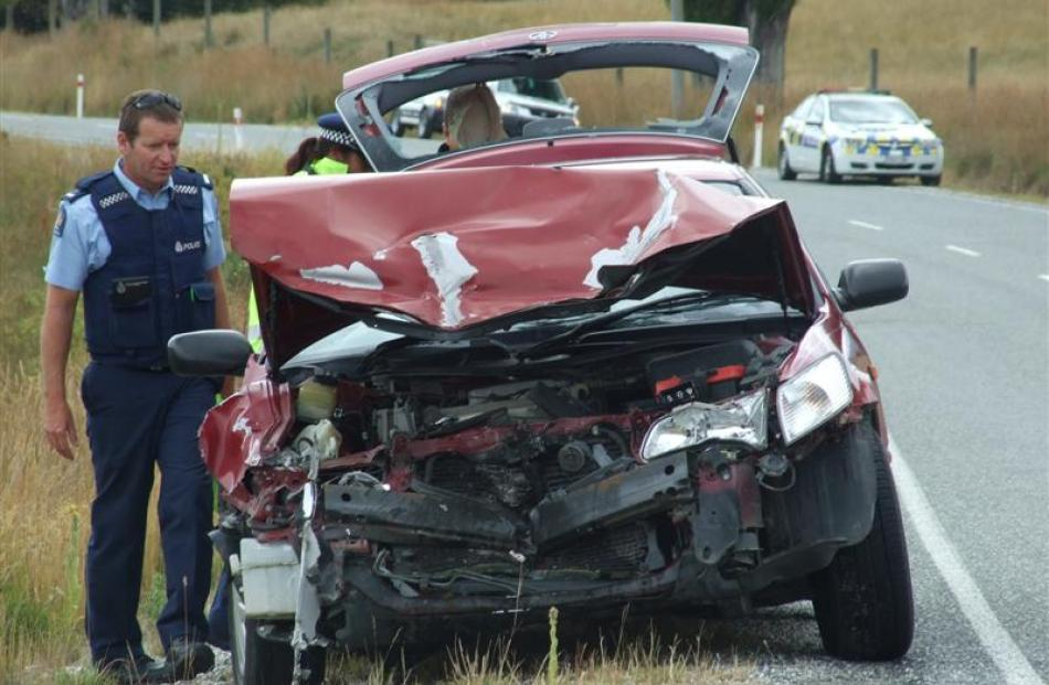 Queenstown police officers inspect the wreckage of a German couple's Toyota Camry rental car,...