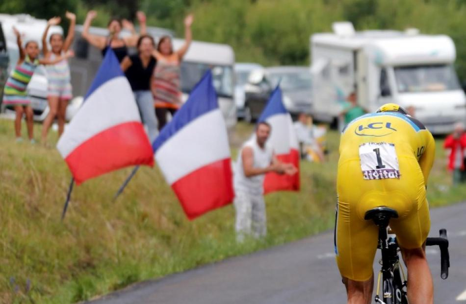 Race leader Chris Froome of Britain cycles past spectators to win the 32km individual time-trial...