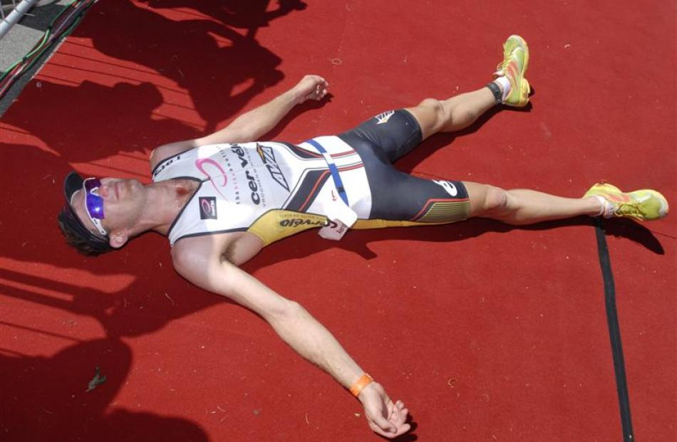 Race winner Aaron Farlow, from Australia, collapses at the finish of Challenge Wanaka 2012. After...
