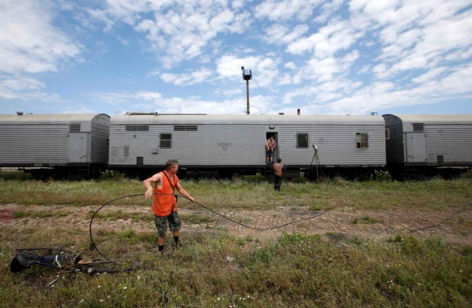 Railway employees work near refrigerator wagons, said to contain bodies of passengers of the...