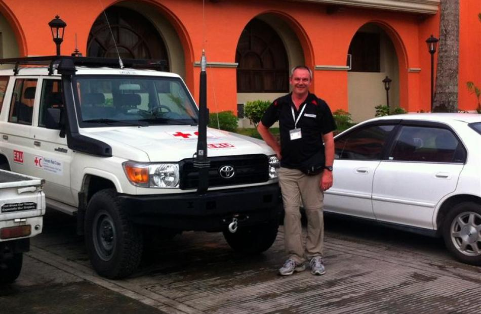 Red Cross humanitarian worker Glenn Mitchell, of Dunedin, in Ormoc on Leyte Island with one of...