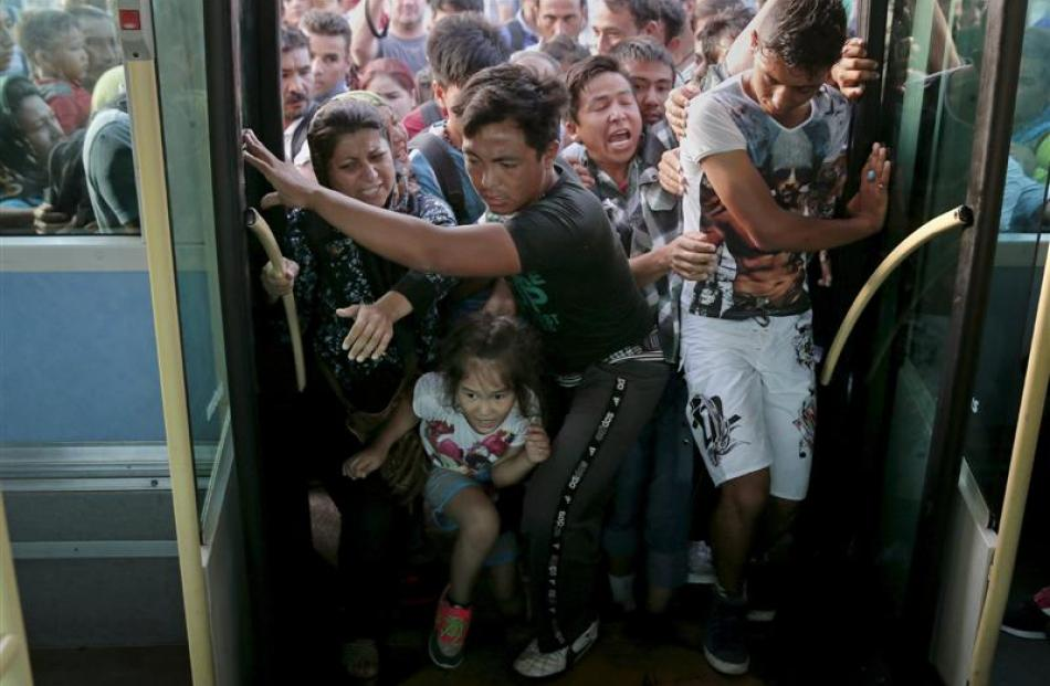 Refugees and migrants push and jostle as they try to board a bus this week  following their...
