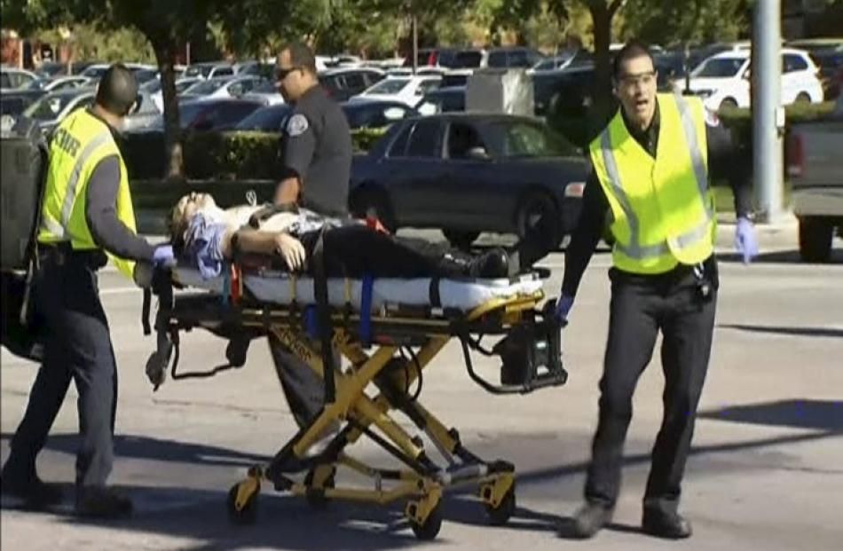 Rescue crews tend to the injured outside the Inland Regional Center in this still image taken...
